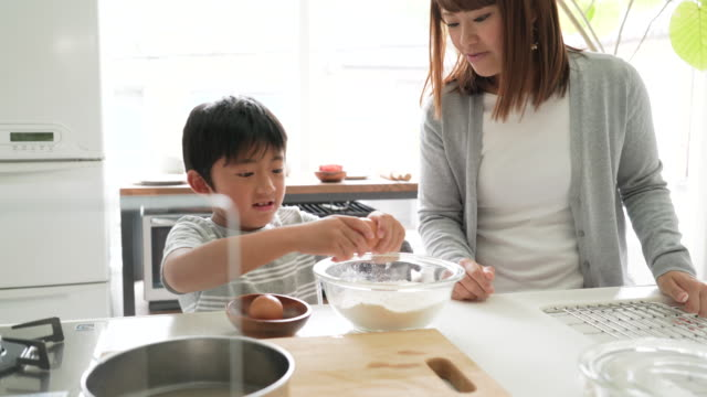 Mother and son cooking together in the kitchen video