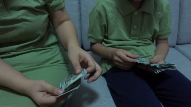 Mother and son counting dollar bill money