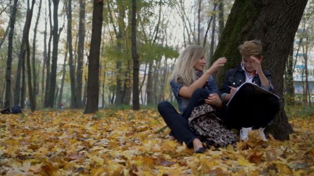 mor och son gör läxor i höst park - linjerat papper bakgrund bildbanksvideor och videomaterial från bakom kulisserna