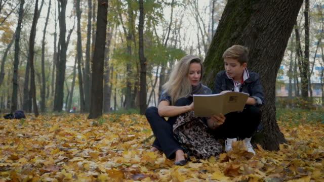 mor och son gör läxor sitter på höstlöv på marken i parken - linjerat papper bakgrund bildbanksvideor och videomaterial från bakom kulisserna