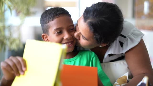 anne ve oğlu kucaklayan ve hediyeler - anneler veya çocuk günü alma - erkek çocuklar stok videoları ve detay görüntü çekimi
