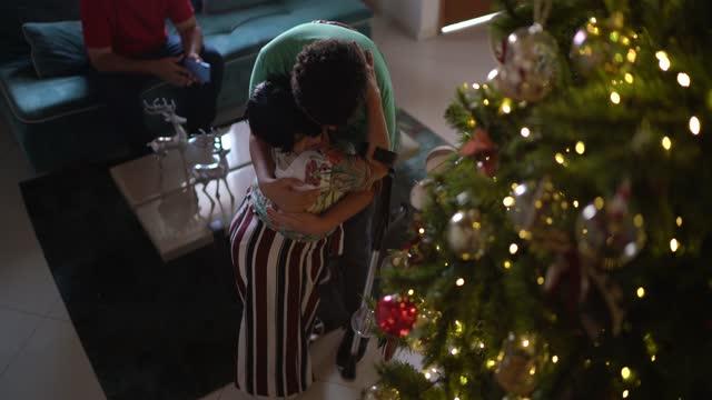 クリスマスツリーを飾りながら抱き合う母と息子 - disabilitycollection点の映像素材/bロール