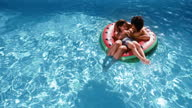 istock Mother and son floating in swim ring in a pool 1287227105