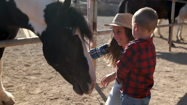 Mother and son having fun at farm ranch cuddling a horse