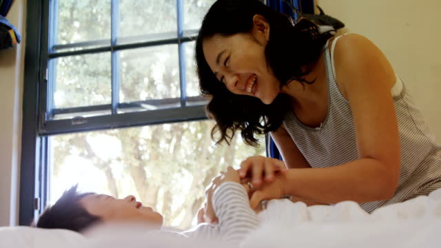 Mother and son having fun on bed in bedroom 4k video