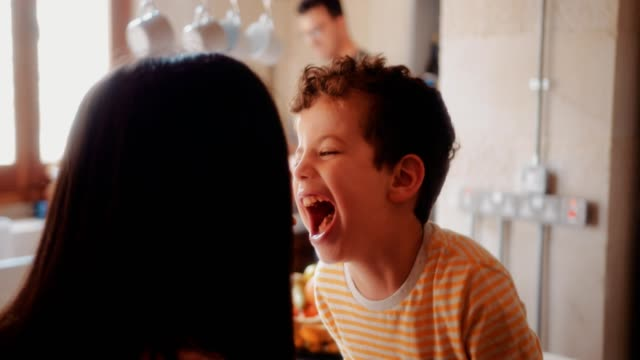 Mother and son having fun with breakfast in house kitchen video