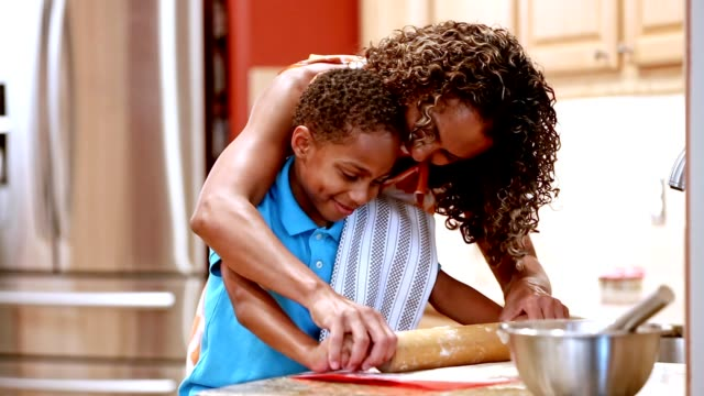 Mother and son in kitchen baking cookies. video