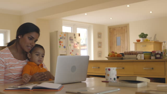 Mother And Son In Kitchen Looking At Laptop Together video