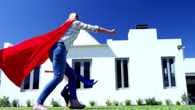 Mother and son in superhero costume having fun in garden 4k video