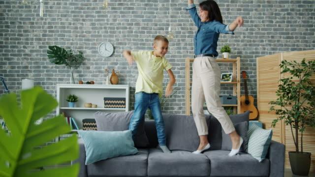 mutter und sohn springen auf sofa zu hause spaß zusammen entspannen lachen - achtlos stock-videos und b-roll-filmmaterial