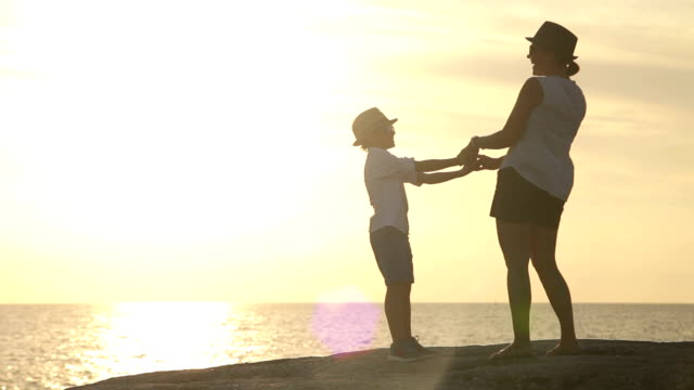 Mother and son laughing on the seashore with great sunset video