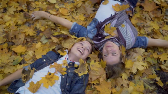 Mother and son lays on the ground and throws autumn leaves Slowmotion. Pretty boy with his mother lies on the ground in the light autumn forest. Mother and her son enjoy the leisure and throw autumn leaves in one another. People enjoy the leisure. Mom touches her son. lying down stock videos & royalty-free footage