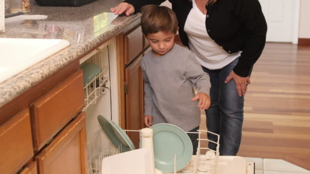 Mother and Son loading dishwasher together video