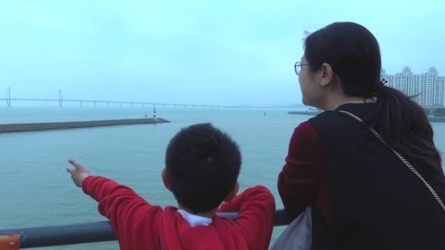 mother and son looking hong kong-zhuhai-macau bridge on tourboat - zhuhai video stock e b–roll