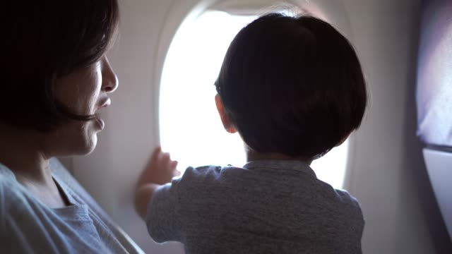 Mother and son looking shots in airplane video