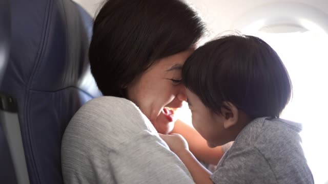 Mother and son looking shots in airplane