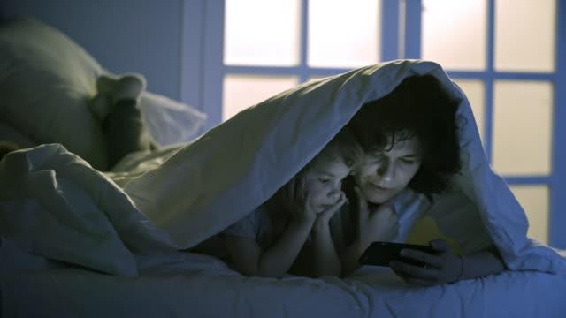 mother and son lying under blanket - kołdra filmów i materiałów b-roll