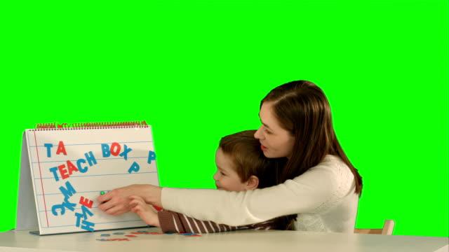 stockvideo's en b-roll-footage met moeder en zoon maken woord mama op het bureau op een groen scherm - birthday gift voucher