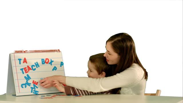 stockvideo's en b-roll-footage met moeder en zoon maken word mama op het bureau op witte achtergrond geïsoleerd - birthday gift voucher