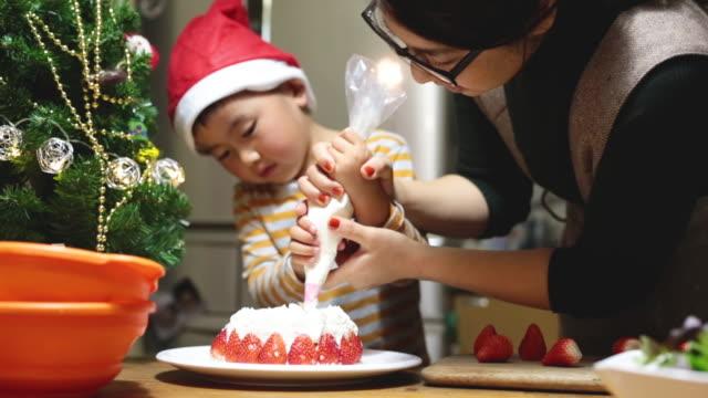 vídeos de stock e filmes b-roll de mother and son making a christmas cake at home - christmas cake
