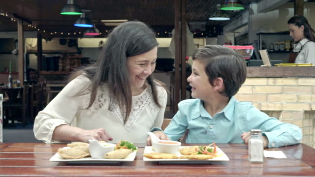 Mother and son of Latin ethnicity of different ages is sharing lunch in a restaurant
