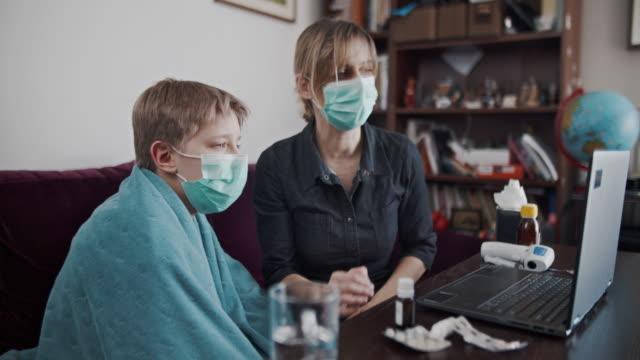 мать и сын по телемедицине видеозвонок с врачом - дистанционный стоковые видео и кадры b-roll