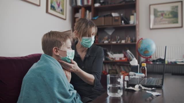stockvideo's en b-roll-footage met moeder en zoon op telemedicine videogesprek met arts - ver