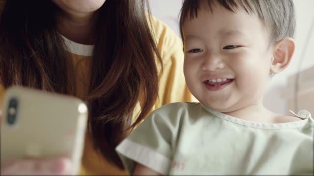 母と父の病院とビデオ通話の息子。 - 注視する点の映像素材/bロール