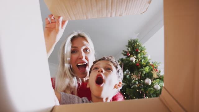 mor och son öppning närvarande på juldagens morgon sedd inifrån box - christmas present bildbanksvideor och videomaterial från bakom kulisserna