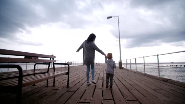 Mother and son playfully walking on wooden pier video