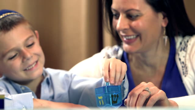 Mother and son playing dreidel video