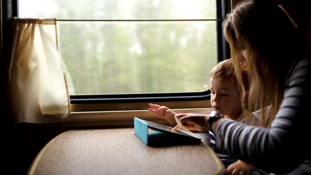 Mother and son playing game on touchpad in the train video