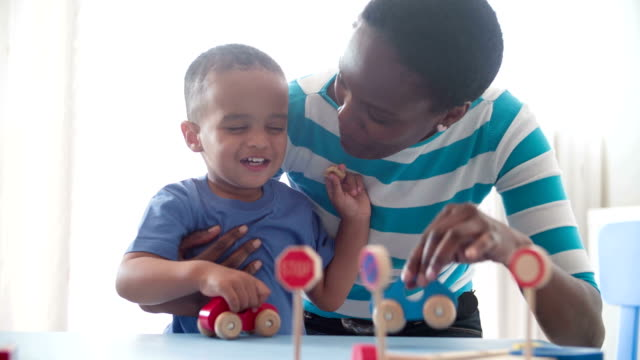 Mother and son playing with wooden toy cars at home. video
