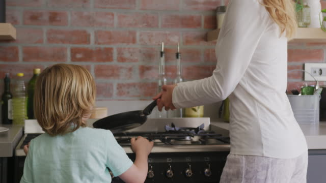 vídeos de stock e filmes b-roll de mother and son preparing food in kitchen at comfortable home 4k - cooker happy