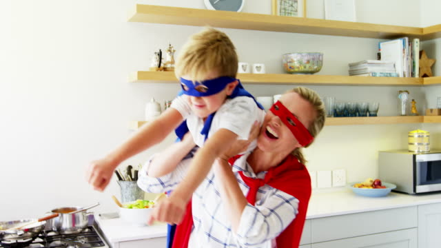 Mother and son pretending to be superhero in living room 4k video