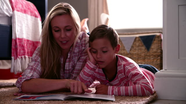 Mother And Son Reading Book In Child's Bedroom video