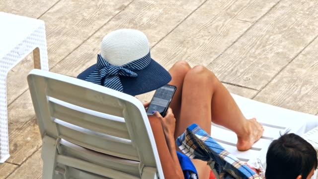 mutter und sohn entspannung im liegestuhl in der nähe pool im resort - sun chair stock-videos und b-roll-filmmaterial
