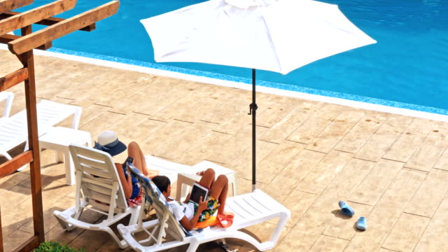 Mother and son relaxing at sunbed near pool at resort Mother and son relaxing at sunbed near pool at resort. Child and mom sunbathe. Fashion girls, friends, family at resort lounge chair stock videos & royalty-free footage