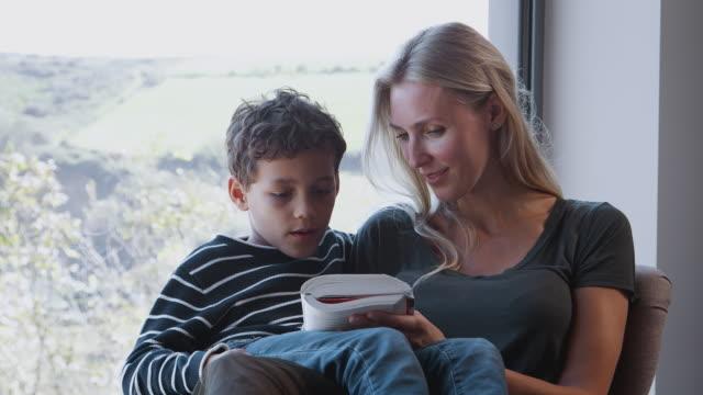mor och son koppla av i stolen genom fönstret hemma läsning bok tillsammans - stavning bildbanksvideor och videomaterial från bakom kulisserna
