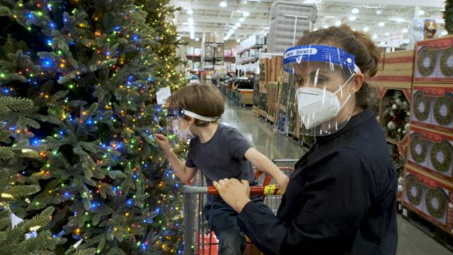 anne ve oğlu koruyucu yüz maskeleri giyen bir mağazada noel ağaçları için alışveriş - çocuk bayramı stok videoları ve detay görüntü çekimi