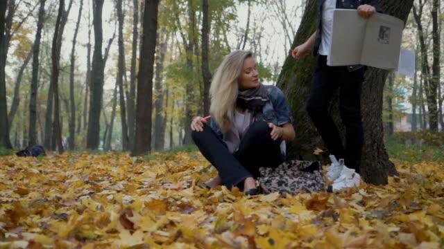 mor och son sitter under trädet på höstlöv i park - linjerat papper bakgrund bildbanksvideor och videomaterial från bakom kulisserna