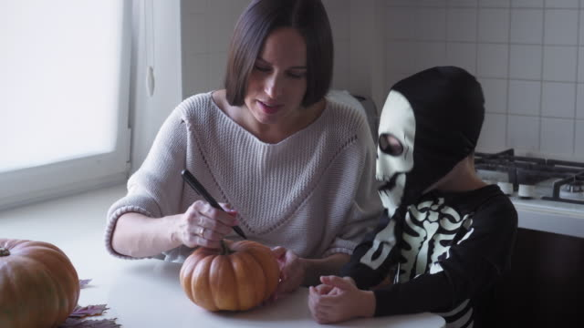 Mother and son sketching the jack-o-lantern face on pumpkin video