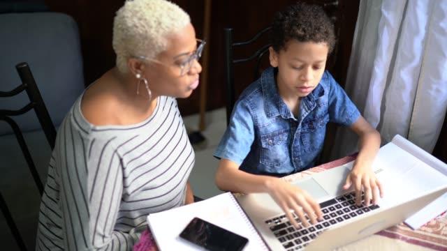 madre e figlio che studiano con il laptop in una lezione online a casa - parenting video stock e b–roll