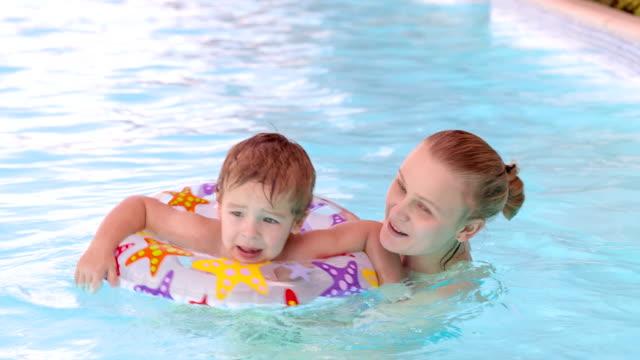 mother and son swimming in the pool - inflatable ring bildbanksvideor och videomaterial från bakom kulisserna