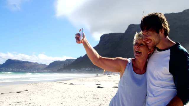Mother and son taking selfie from mobile phone at beach video