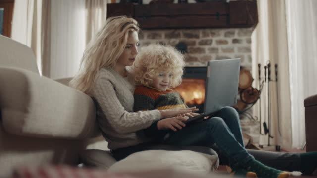 stockvideo's en b-roll-footage met moeder en zoon die laptop samen gebruiken - blond curly hair