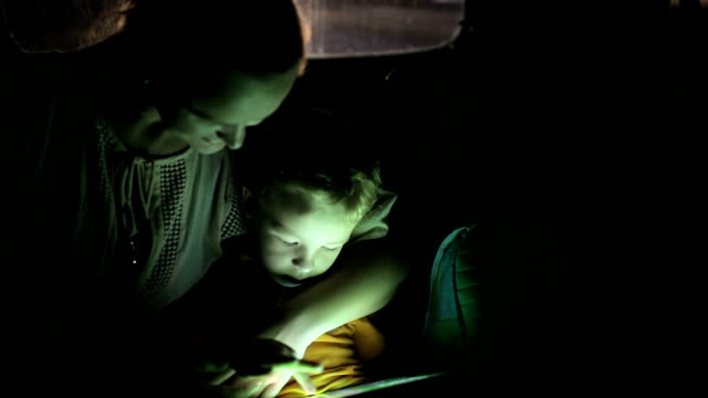 Mother and son using touch pad in car at night video