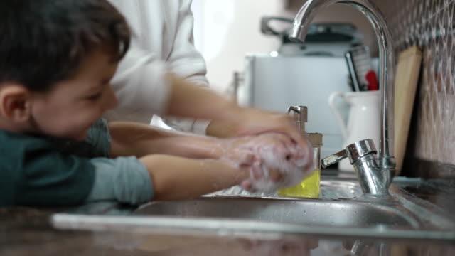 mor och son wahing händer tillsammans i köket - washing hands bildbanksvideor och videomaterial från bakom kulisserna