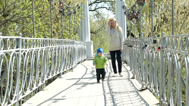 Mother and son walking on a bridge in a park