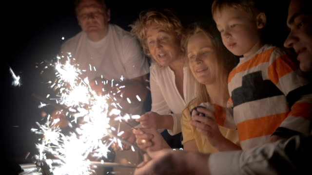 Mother and son with sparklers at night video